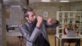 El hombre de negocios feliz con la barba está bailando en la oficina, sonriendo, colegas está aplaudiendo, trabaja concepto, rela almacen de video