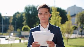 El hombre de negocios feliz joven en un traje elegante examina cuidadosamente los papeles al aire libre Forma de vida acertada, c metrajes