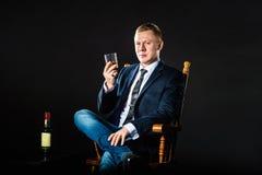 El hombre de negocios feliz levanta el vidrio de whisky y mira en la cámara imagen de archivo libre de regalías