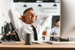 El hombre de negocios feliz que se sienta en la oficina que trabaja con el ordenador tiene un resto fotografía de archivo