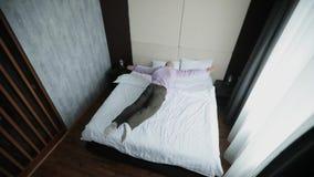 El hombre de negocios feliz salta en cama en la habitación de tener un resto metrajes