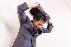 El hombre de negocios frustrado furioso pierde genio con el ordenador portátil imagen de archivo
