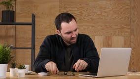 El hombre de negocios frustrado que lleva a cabo su cabeza se sienta en la oficina almacen de video