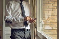 El hombre de negocios golpea ligeramente el teléfono elegante móvil Imágenes de archivo libres de regalías