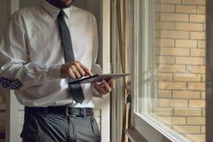 El hombre de negocios golpea ligeramente la tableta digital Foto de archivo libre de regalías