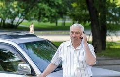 El hombre de negocios habla cerca de su vehículo Imagen de archivo libre de regalías