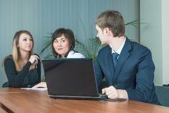 El hombre de negocios habla con los colegas en oficina Imagen de archivo libre de regalías