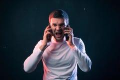 El hombre de negocios habla en dos teléfonos y gritos del agotamiento extremo y imagen de archivo libre de regalías