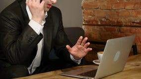 El hombre de negocios habla en smartphone en café El hombre se sienta en la tabla en café y habla en el teléfono celular, mentira almacen de metraje de vídeo
