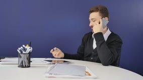 El hombre de negocios habla en el teléfono en la oficina almacen de video