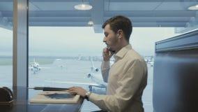 El hombre de negocios habla en el teléfono en el pasillo del aeropuerto metrajes