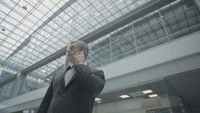 El hombre de negocios habla en el teléfono en el pasillo del aeropuerto almacen de metraje de vídeo