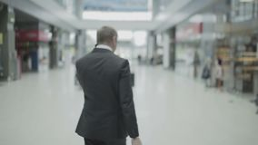 El hombre de negocios habla en el teléfono y sale con la maleta en el aeropuerto almacen de video