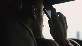El hombre de negocios habla por el teléfono móvil que se sienta en coche almacen de metraje de vídeo