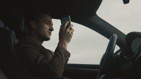 El hombre de negocios habla por el teléfono que se sienta en coche almacen de metraje de vídeo