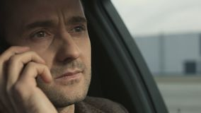 El hombre de negocios habla por el teléfono que se sienta en primer del coche almacen de metraje de vídeo