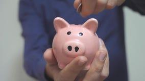 El hombre de negocios hace ahorros de la forma de vida pone monedas en una hucha Concepto del negocio de la hucha vídeo de la cám metrajes