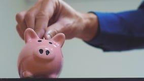 El hombre de negocios hace ahorros pone monedas en una hucha Concepto del negocio de la hucha vídeo de la cámara lenta el dinero  almacen de metraje de vídeo