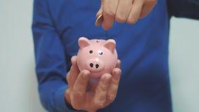 El hombre de negocios hace ahorros pone monedas en una hucha forma de vida del concepto del negocio de la hucha vídeo de la cámar almacen de video