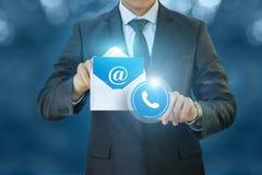 El hombre de negocios hace clic en el icono de los contactos imagenes de archivo