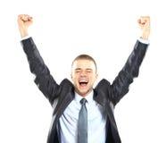 El hombre de negocios hermoso emocionado con los brazos aumentó en éxito Imagen de archivo libre de regalías