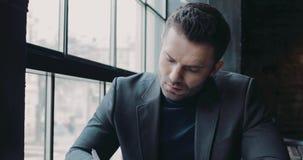 El hombre de negocios hermoso en un equipo formal se sienta en el café y firma los papeles después parece derecho hacia la cámar almacen de video