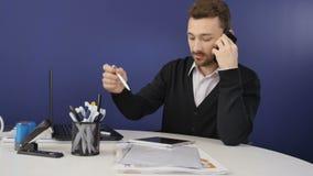 El hombre de negocios hermoso habla en el teléfono en la oficina metrajes