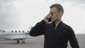 El hombre de negocios hermoso habla en el teléfono en los aviones del od del fondo almacen de metraje de vídeo
