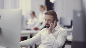 El hombre de negocios hermoso habla por el teléfono y trabaja en el ordenador en la oficina almacen de video