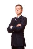 El hombre de negocios hermoso joven en traje negro se está colocando derecho con los brazos cruzados, retrato integral aislado en Imagen de archivo libre de regalías
