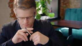 El hombre de negocios hermoso joven está teniendo tiempo que se sienta en la tabla en cafetería metrajes