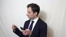 El hombre de negocios hermoso joven incorpora datos de su tarjeta de crédito en el smartphone almacen de video