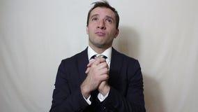 El hombre de negocios hermoso joven ruega, pidiendo a dios ayuda en negocio metrajes