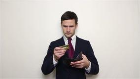 El hombre de negocios hermoso joven saca una tarjeta de crédito del oro de su cartera almacen de video