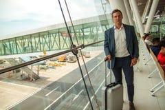 El hombre de negocios hermoso joven se está colocando con una maleta cerca de la ventana en el aeropuerto, esperando su vuelo imagen de archivo libre de regalías
