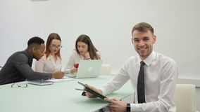 El hombre de negocios hermoso sonríe mientras que lee el informe en su tableta en sitio de co-trabajo metrajes