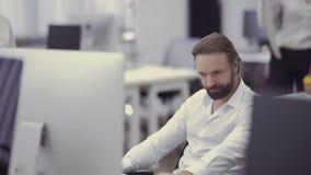 El hombre de negocios hermoso trabaja en el ordenador en la oficina metrajes
