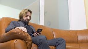 El hombre de negocios hermoso utiliza el teléfono que se sienta en el sofá metrajes