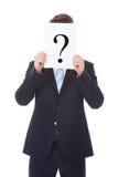 El hombre de negocios Holding Question Mark Sign In Front Of hace frente Foto de archivo libre de regalías