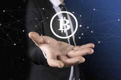 El hombre de negocios irreconocible s da llevar a cabo un holograma redondo del bitcoin Un fondo azul borroso Fotos de archivo