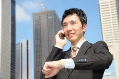 El hombre de negocios japonés habla con un teléfono móvil Fotos de archivo libres de regalías