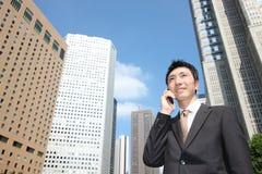 El hombre de negocios japonés habla con un teléfono móvil Foto de archivo libre de regalías