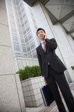 El hombre de negocios japonés habla con un teléfono móvil Imagen de archivo