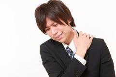El hombre de negocios japonés joven sufre del dolor del cuello Imágenes de archivo libres de regalías