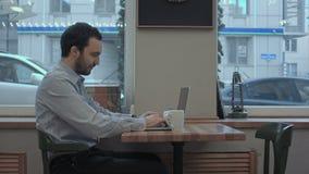 El hombre de negocios joven acertado está trabajando en su ordenador portátil en café y café de consumición metrajes