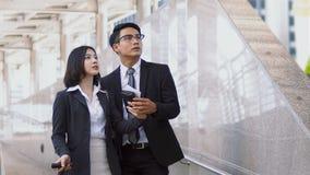 El hombre de negocios joven asiático y la mujer bonita miran encima imagen de archivo