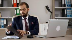 El hombre de negocios joven atractivo en los tipos de la oficina en el ordenador entonces mira en una carpeta con las cartas almacen de metraje de vídeo