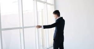 El hombre de negocios joven atractivo está caminando en la ventana Fondo blanco almacen de video