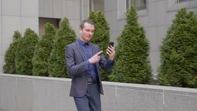 El hombre de negocios joven camina con los auriculares inal?mbricos y lleva agresivamente una discusi?n sobre una llamada video e
