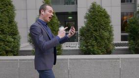 El hombre de negocios joven camina con los auriculares inalámbricos y lleva agresivamente una discusión sobre una llamada video